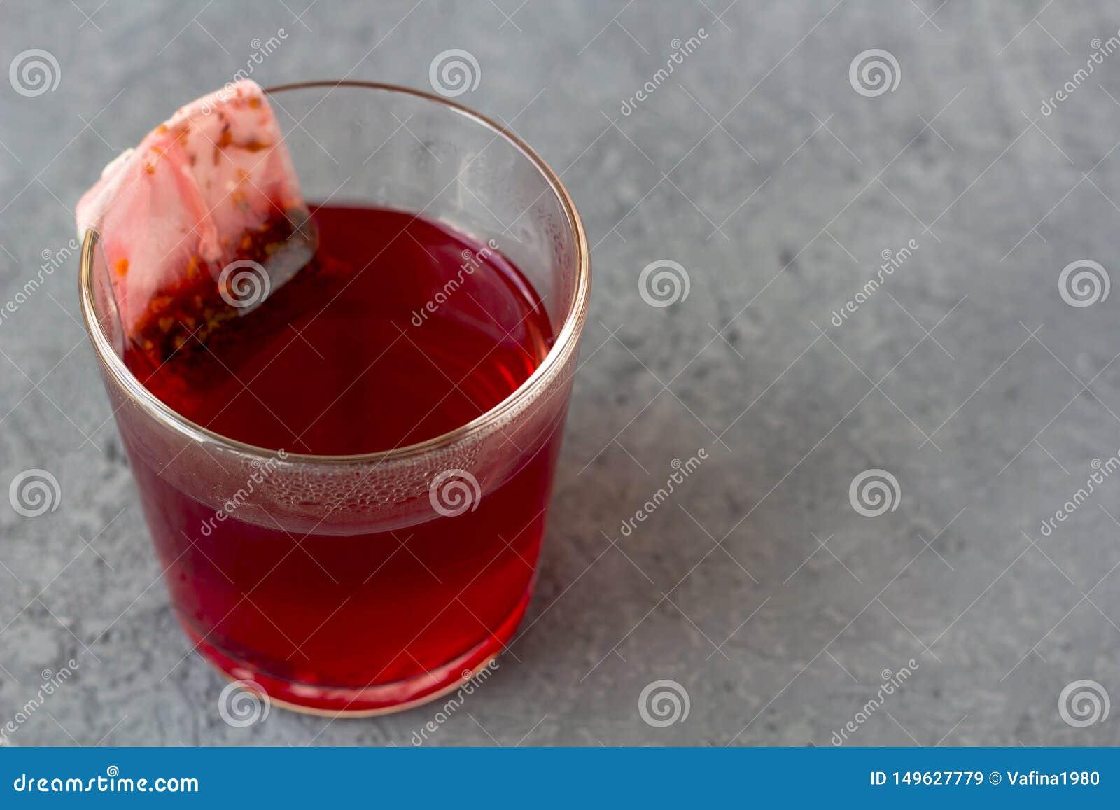 红色木槿karkade,上升了在玻璃的茶袋