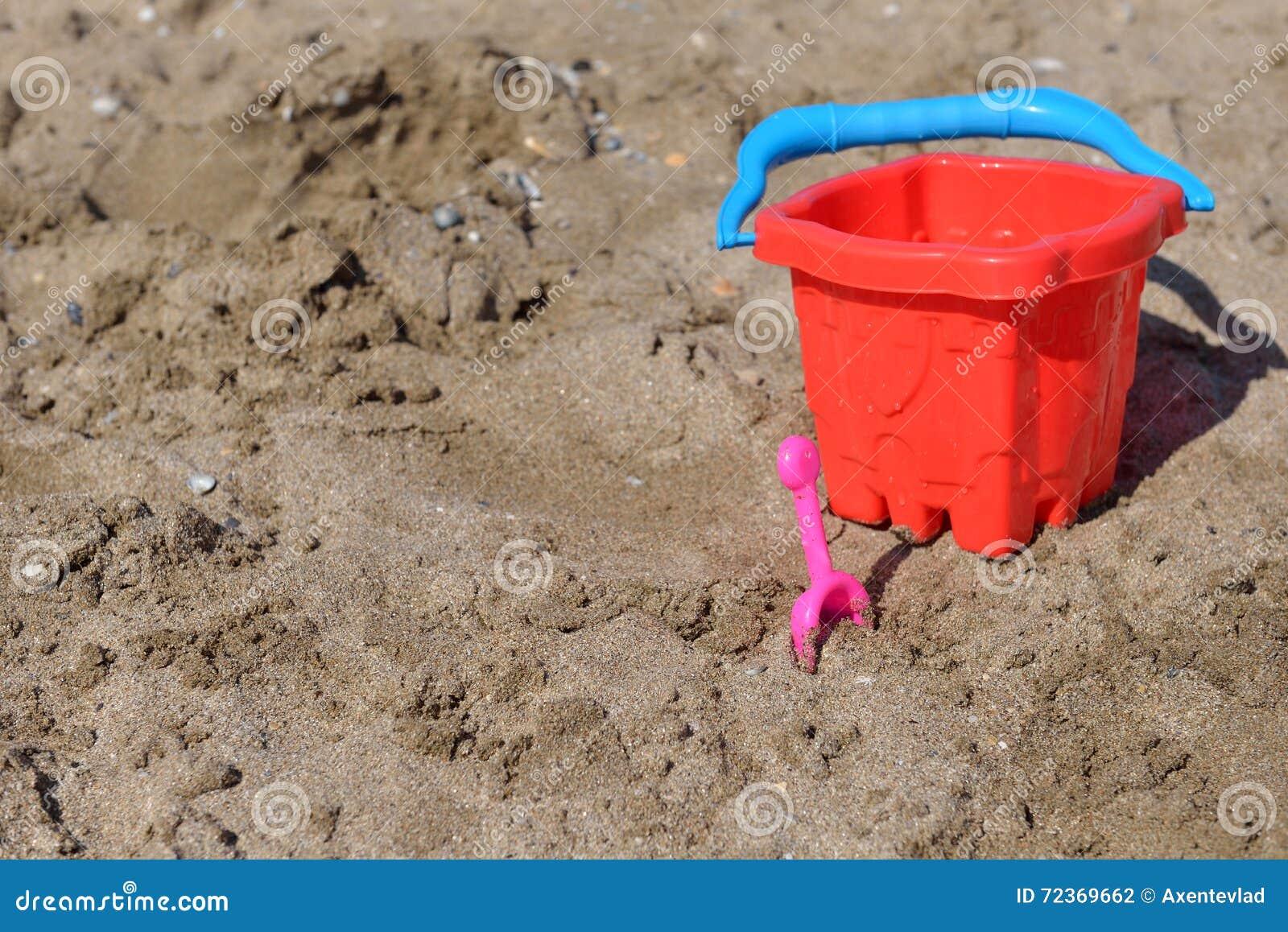 红色桶和小桃红色铁锹在湿沙子在海滩