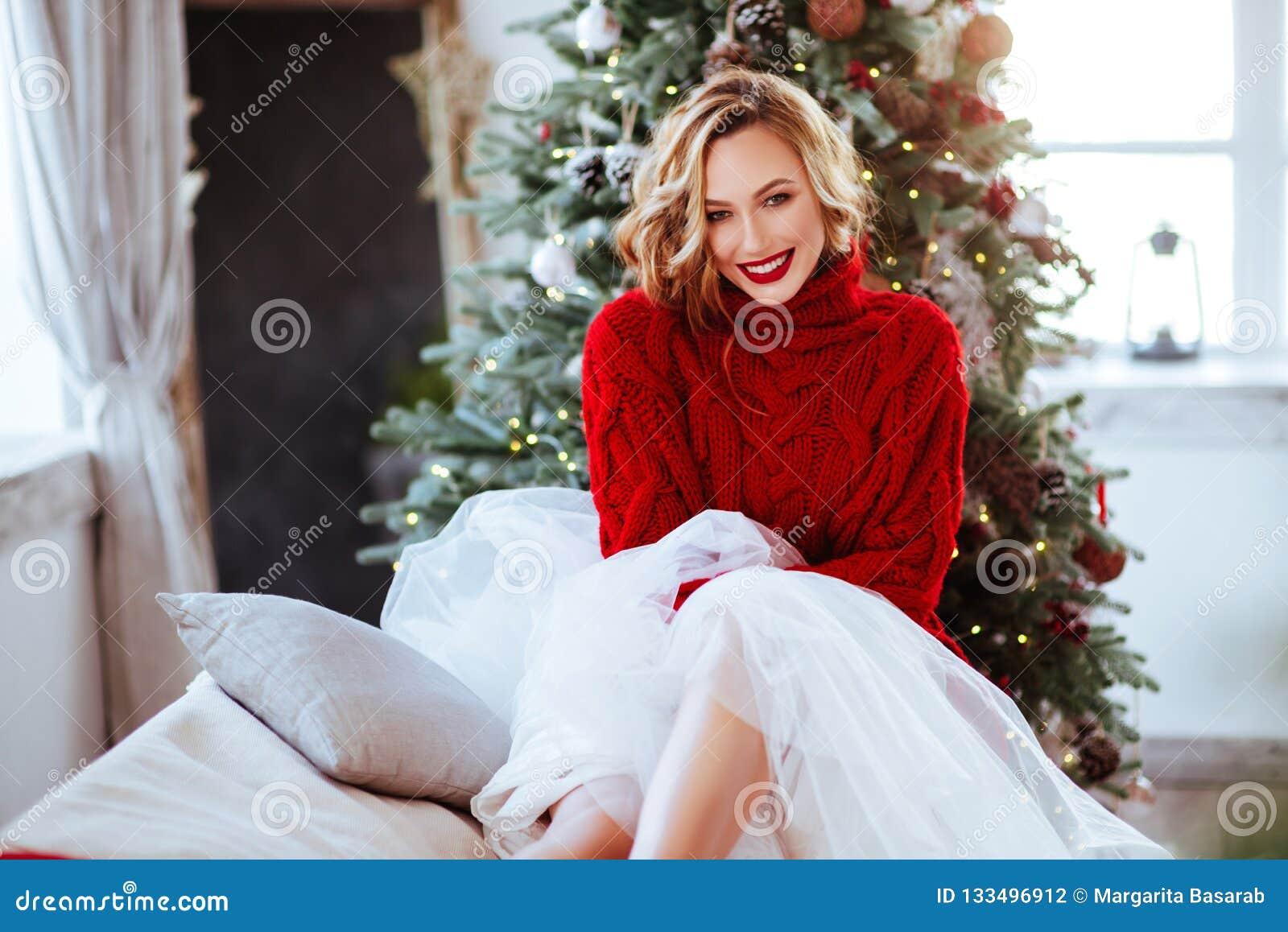红色毛线衣的微笑的妇女在圣诞树背景