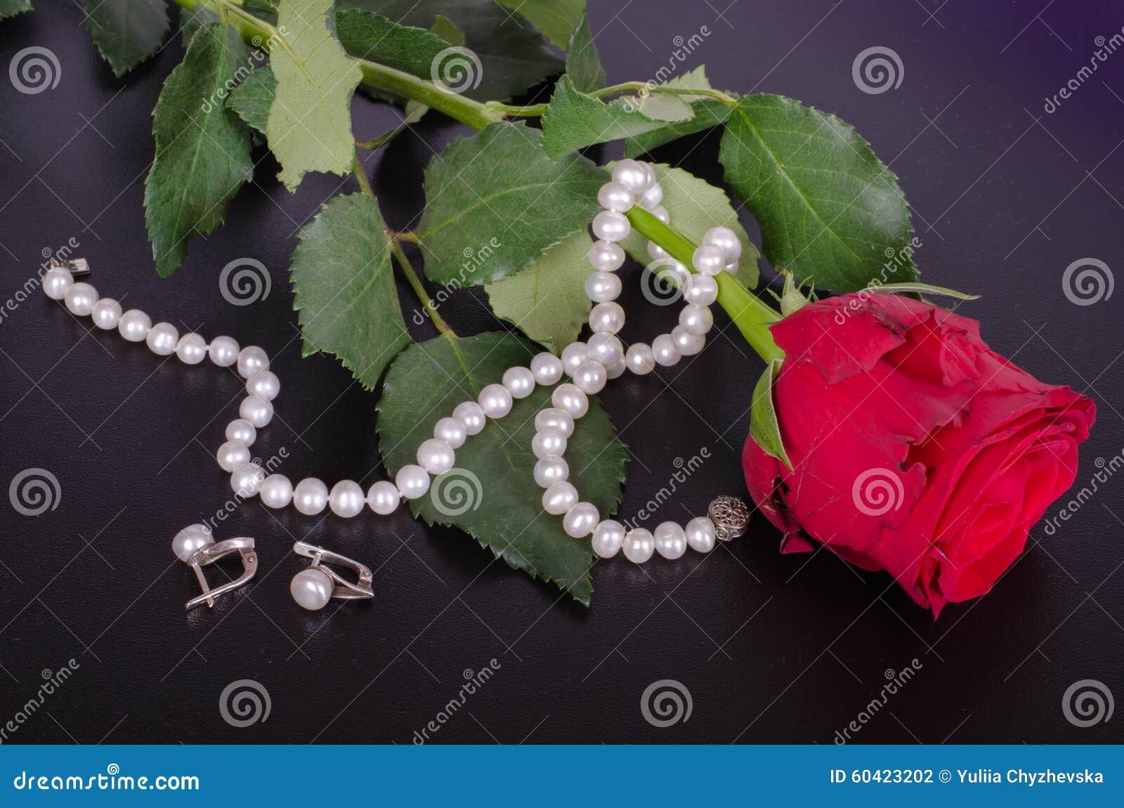 红色玫瑰、珍珠耳环和项链在黑背景