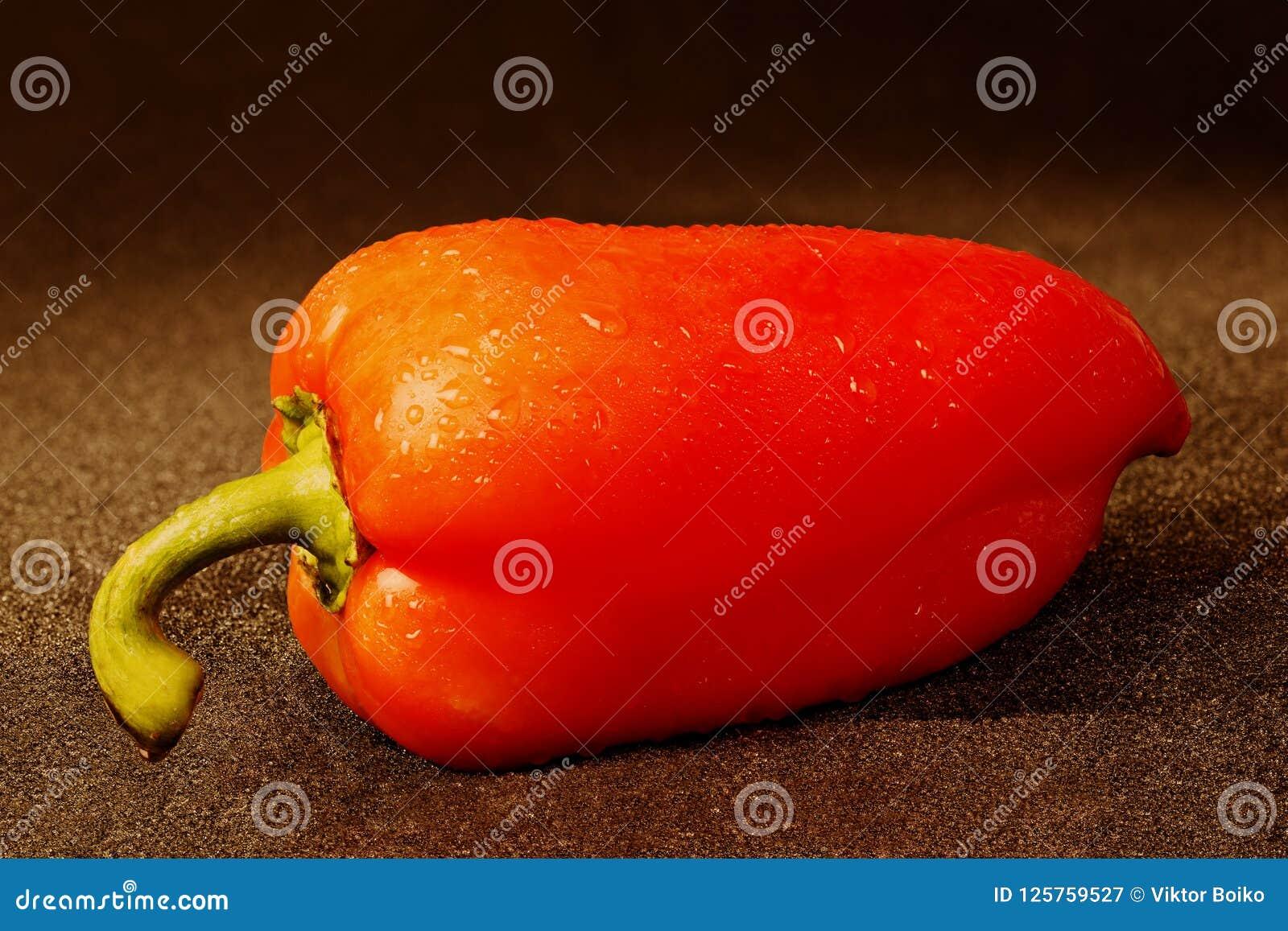红色甜椒有用水洒的黑布料背景滴下