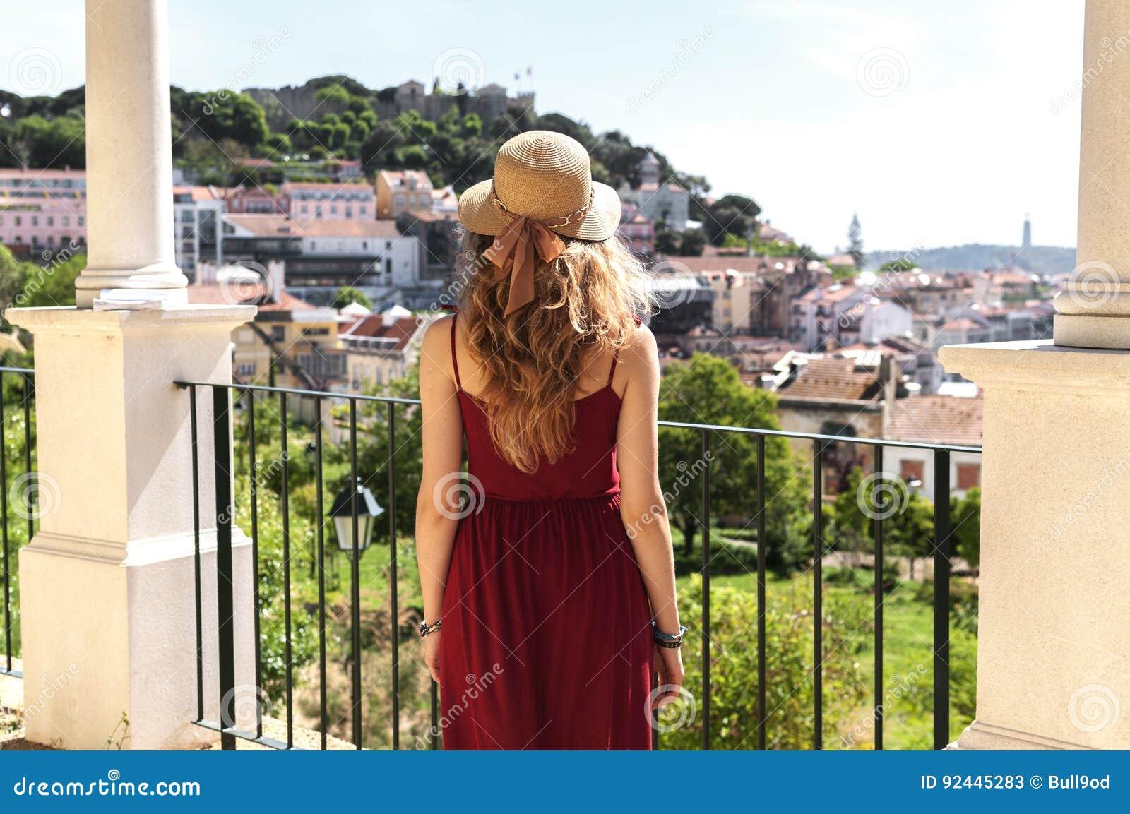红色礼服、太阳帽子和蓝色袋子lookimg的妇女在全景图im里斯本Alfama,葡萄牙
