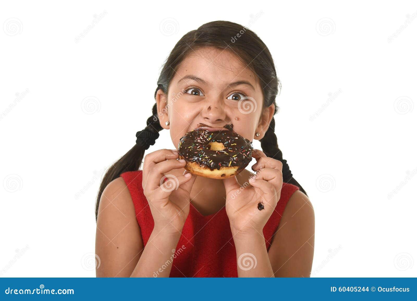 红色礼服的西班牙女孩吃巧克力多福饼用手的和嘴被弄脏的和肮脏微笑愉快