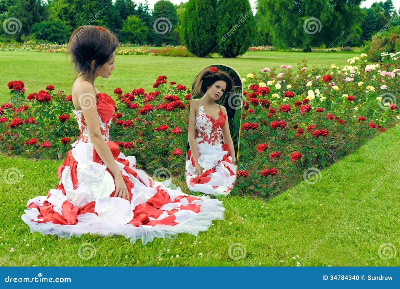 红色礼服神色的一个美丽的女孩在镜子