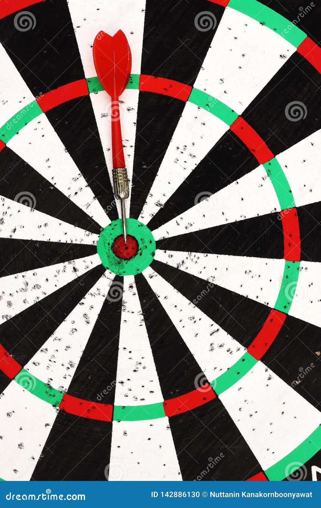 红色箭箭头在掷镖的圆靶背景的目标中心击中了