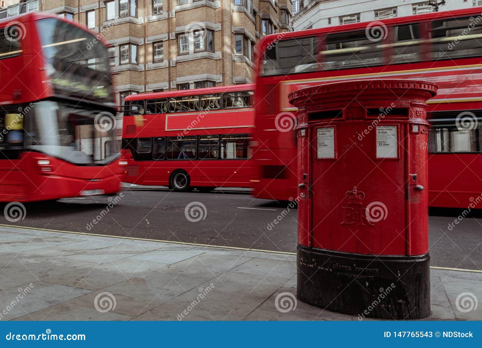 红色邮箱在有通过的双层公共汽车的伦敦