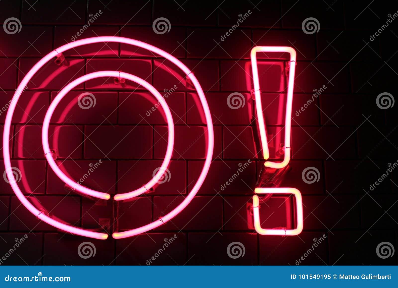 红色霓虹灯信件和感叹号在黑墙壁上