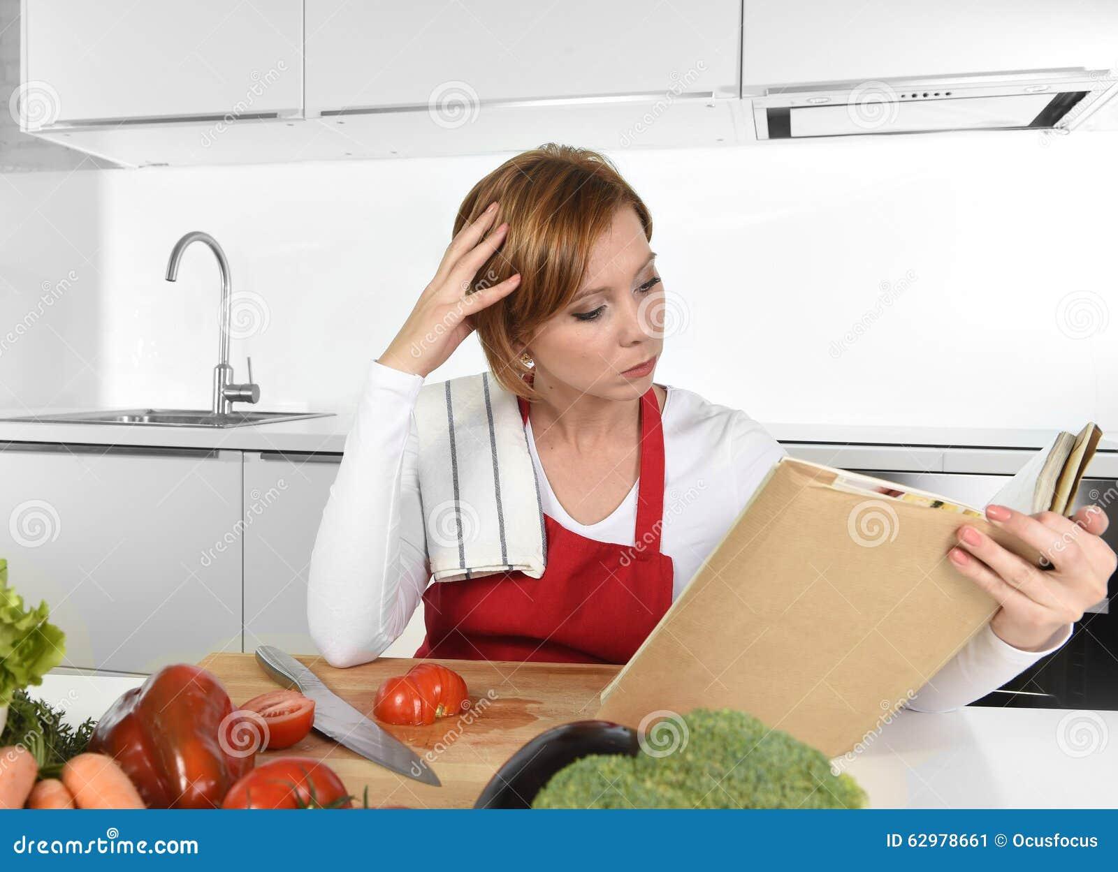 红色围裙的年轻美丽的家庭厨师妇女在现代国内厨房读书菜谱在食谱后
