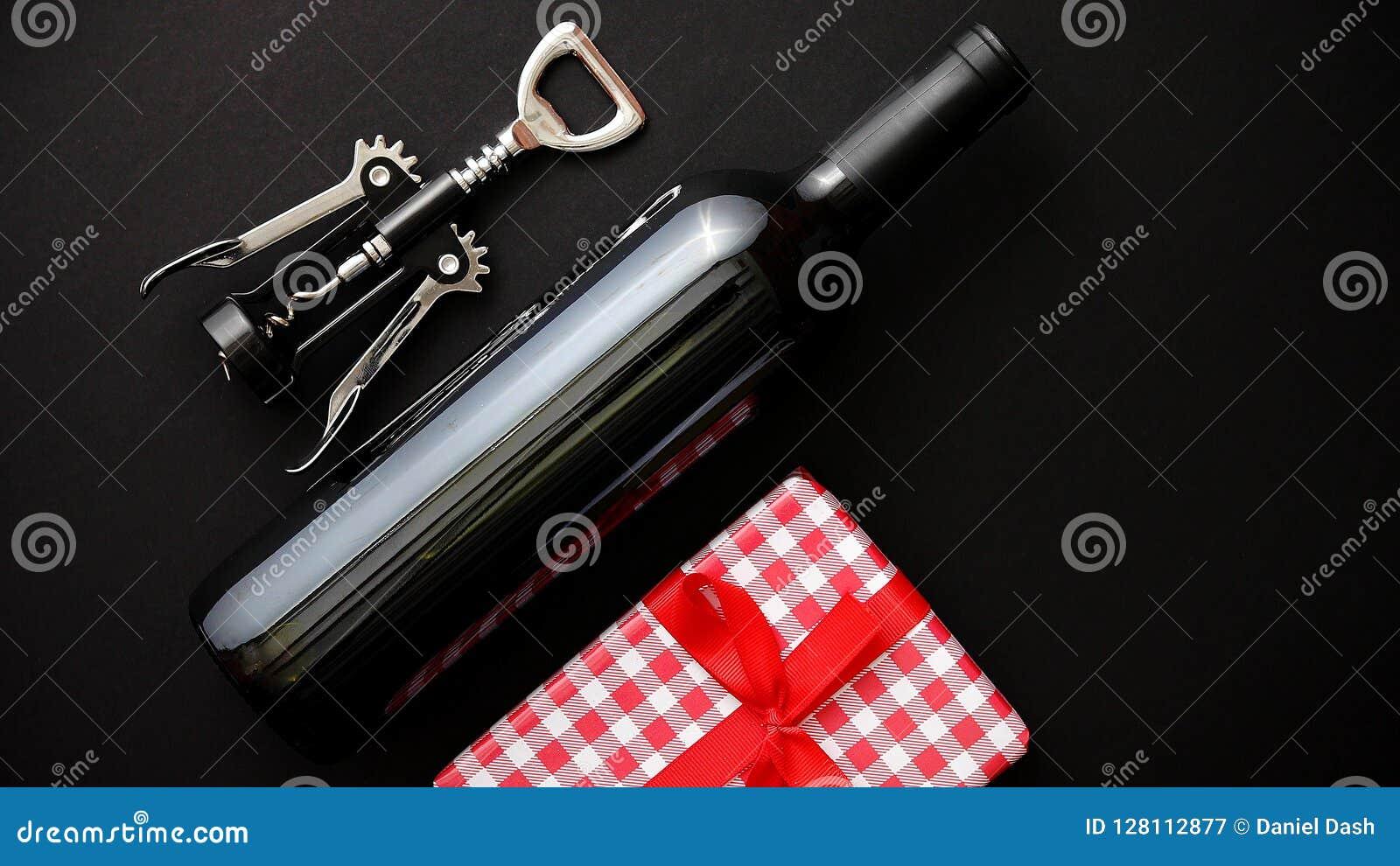红葡萄酒瓶、拔塞螺旋和装箱的圣诞节礼物