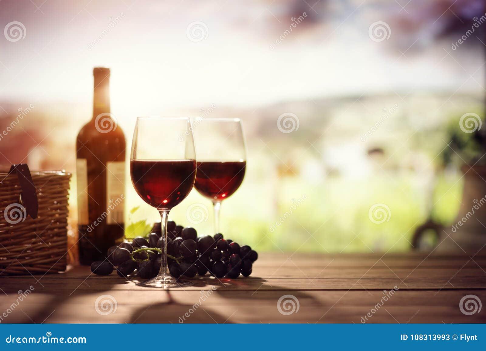 红葡萄酒瓶和玻璃在桌上在葡萄园托斯卡纳意大利里
