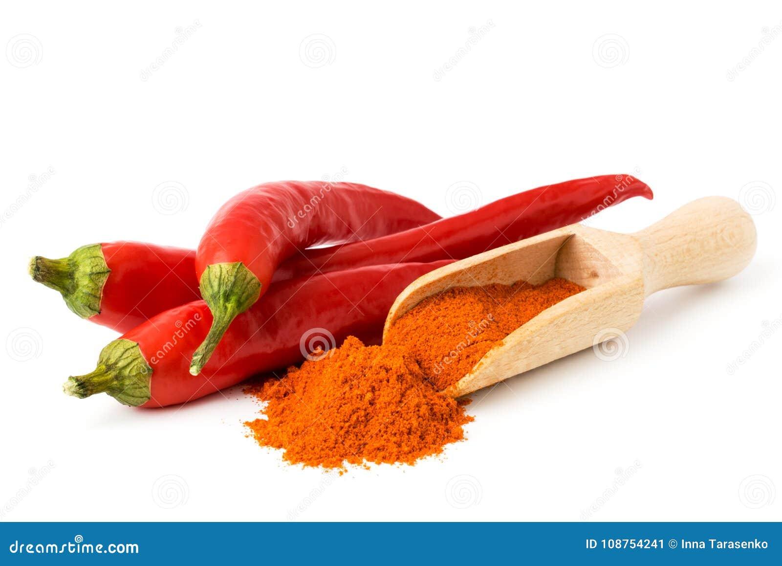 红辣椒和地面在一把木匙子以子弹密击,在白色背景