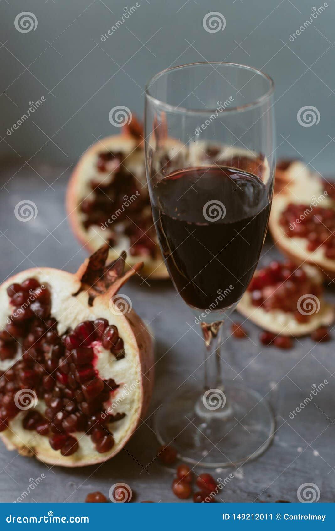 红酒用在织地不很细灰色具体背景的一个开放石榴 一个人倒从瓶的红酒入玻璃