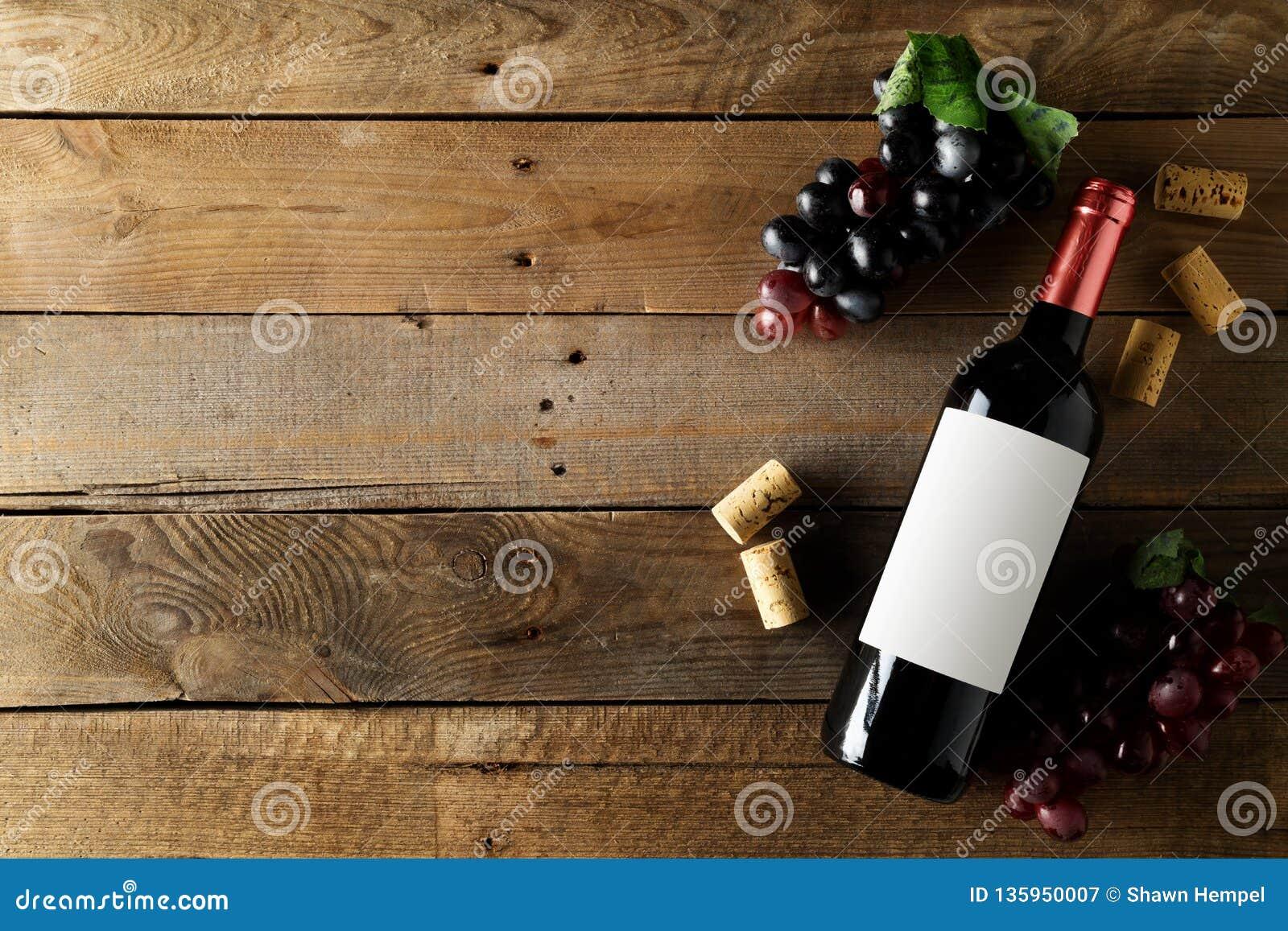 红酒酒瓶用葡萄和黄柏在棕色土气木桌平的位置从上面
