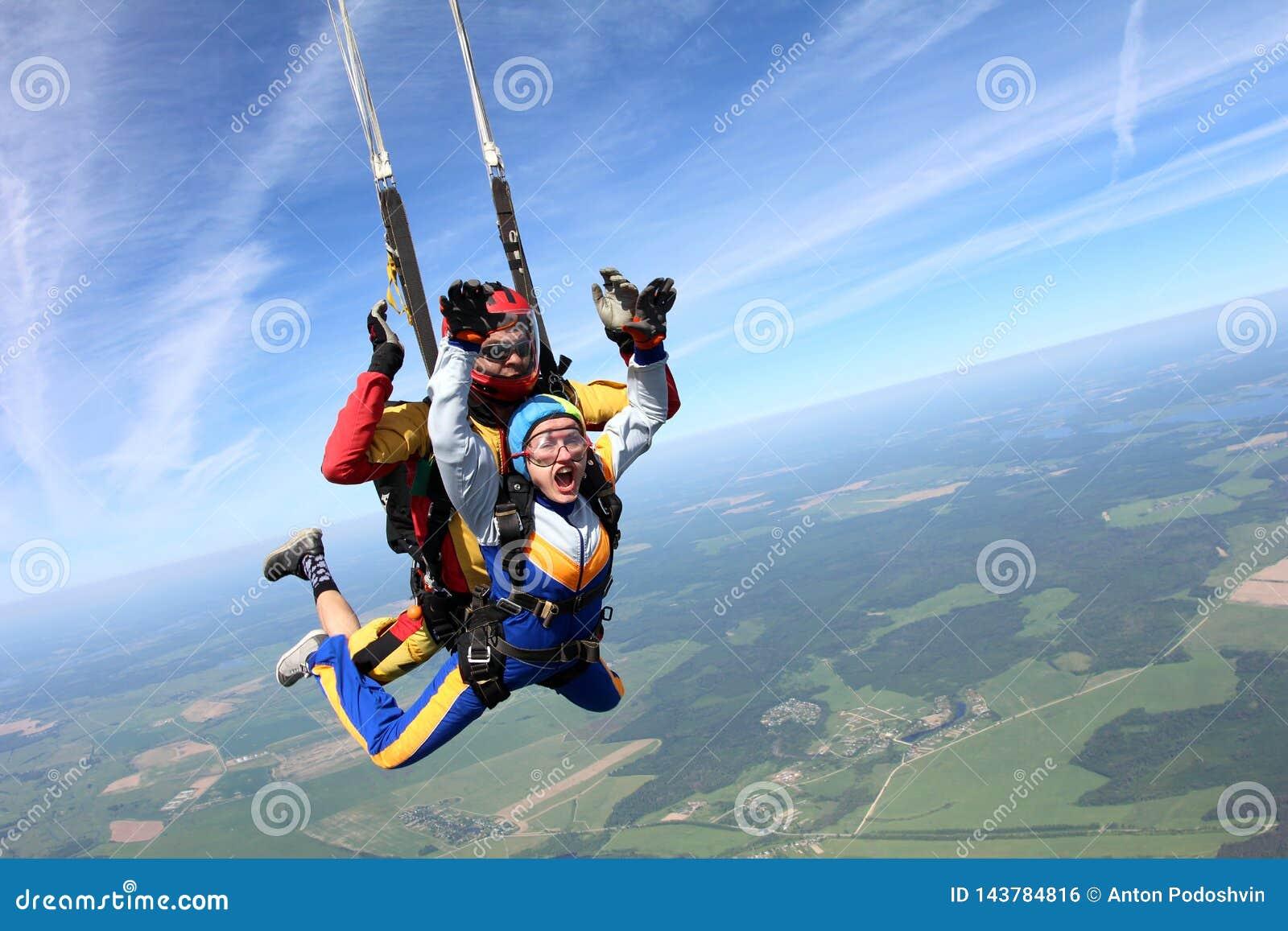 纵排skydiving 妇女和辅导员是在天空