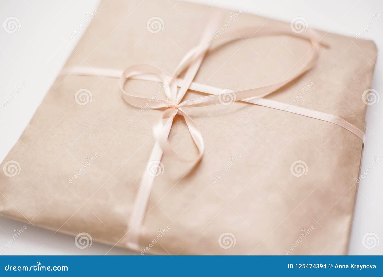 纸板纸盒包裹包裹与浅褐色的纸和栓与在弓的桃红色串丝带