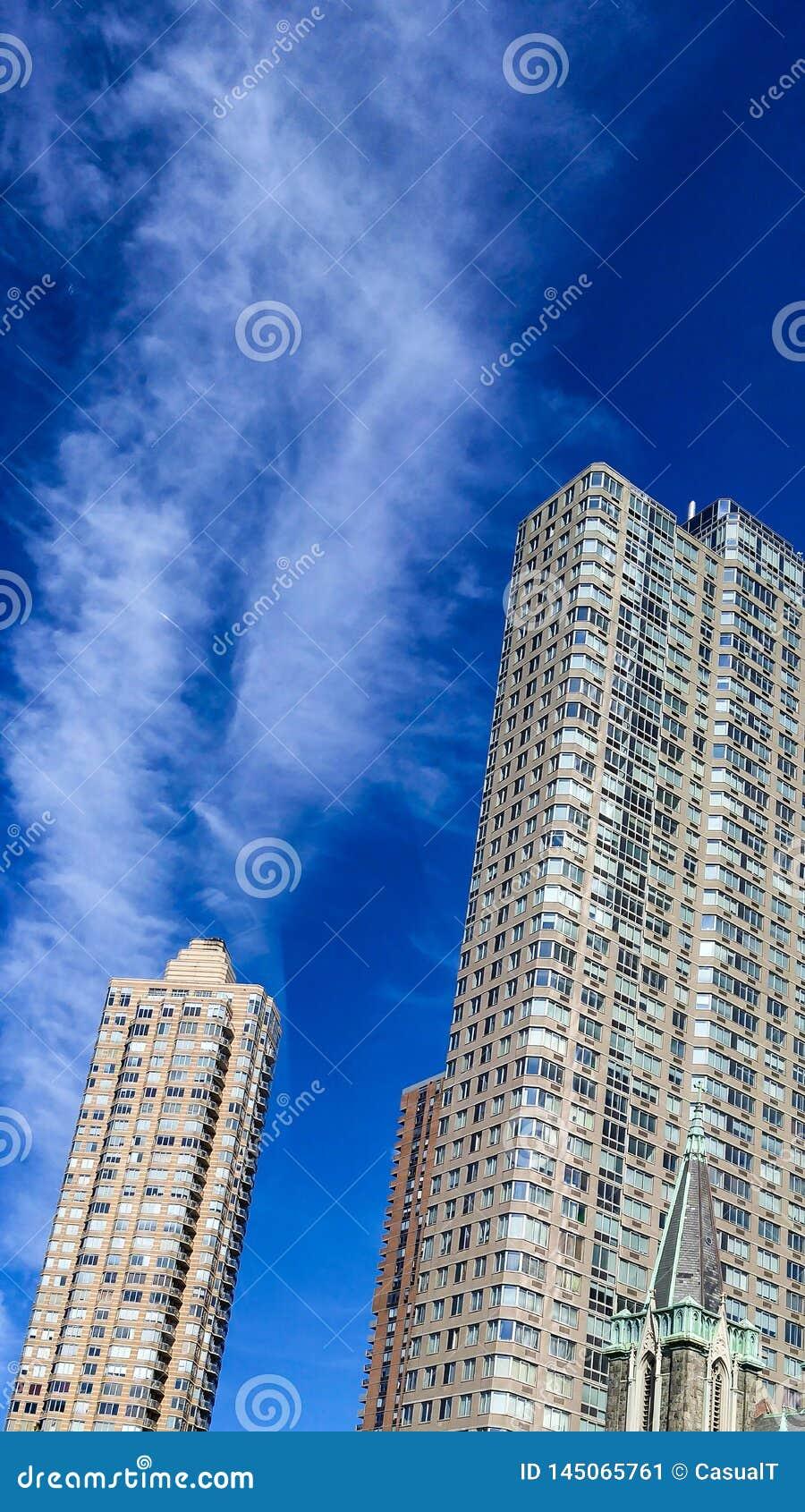 纽约伸手可及的距离的高摩天大楼到至善至美的蓝色夏天天空里