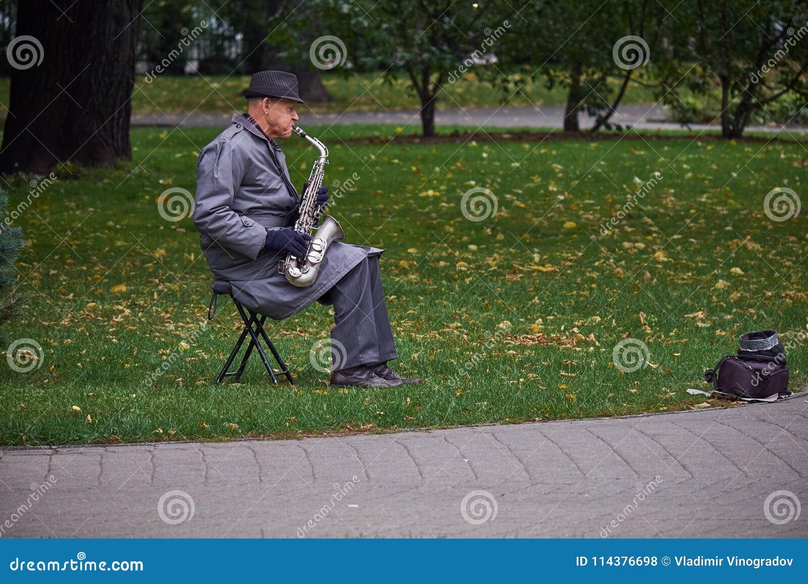纽约,美国- 2017年7月:一件雨衣和一支帽子plaing的萨克斯管的老人在公园