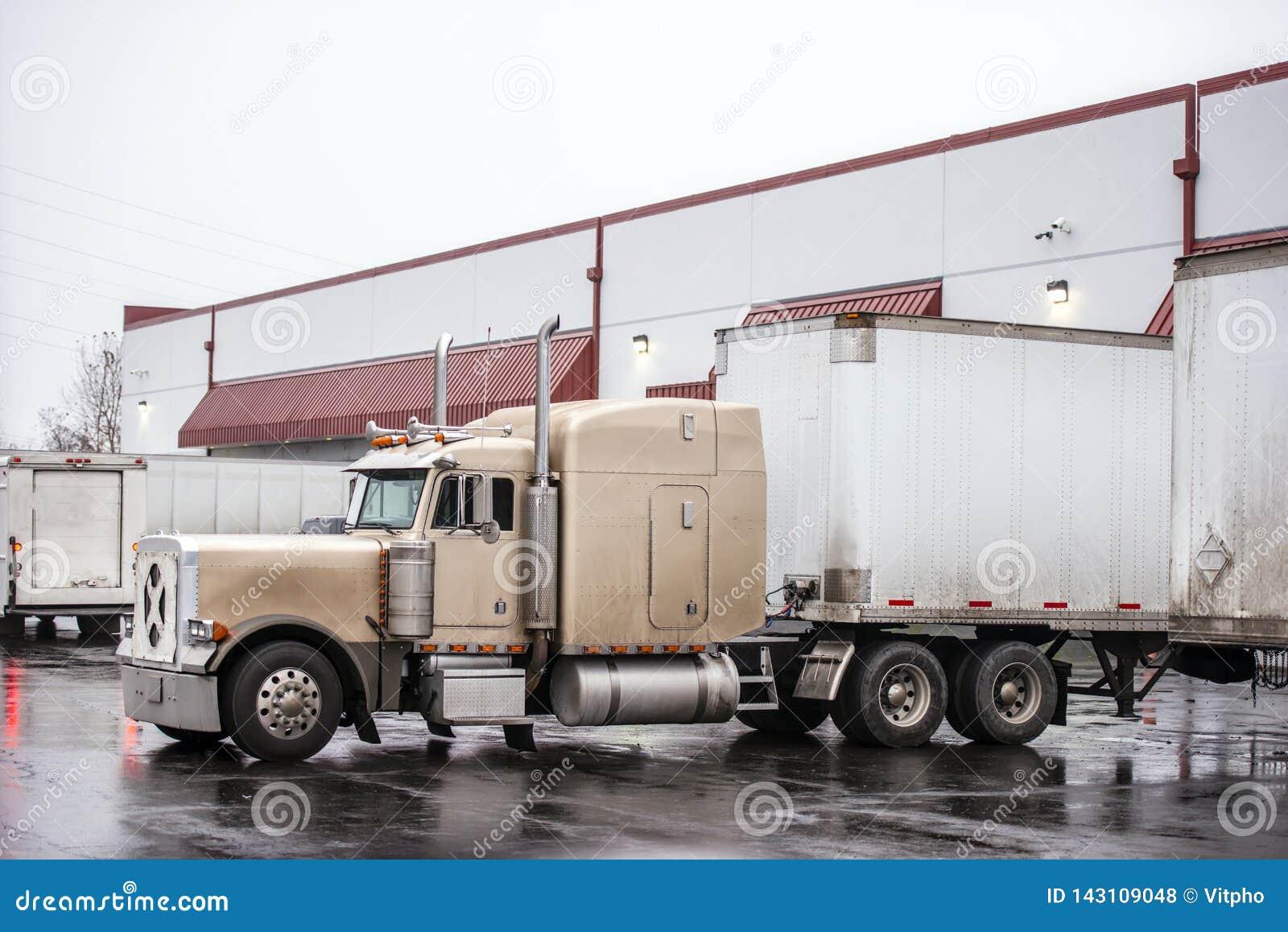 经典大半半船具卡车装载的货物在行的仓库船坞与在湿停车场的另一辆拖车