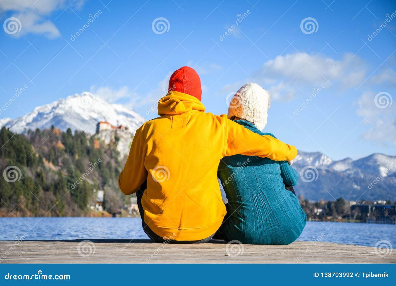 结合在拥抱与五颜六色的布料一起的爱和放松坐在清楚的天空晴朗的冬日图fr的一个木码头