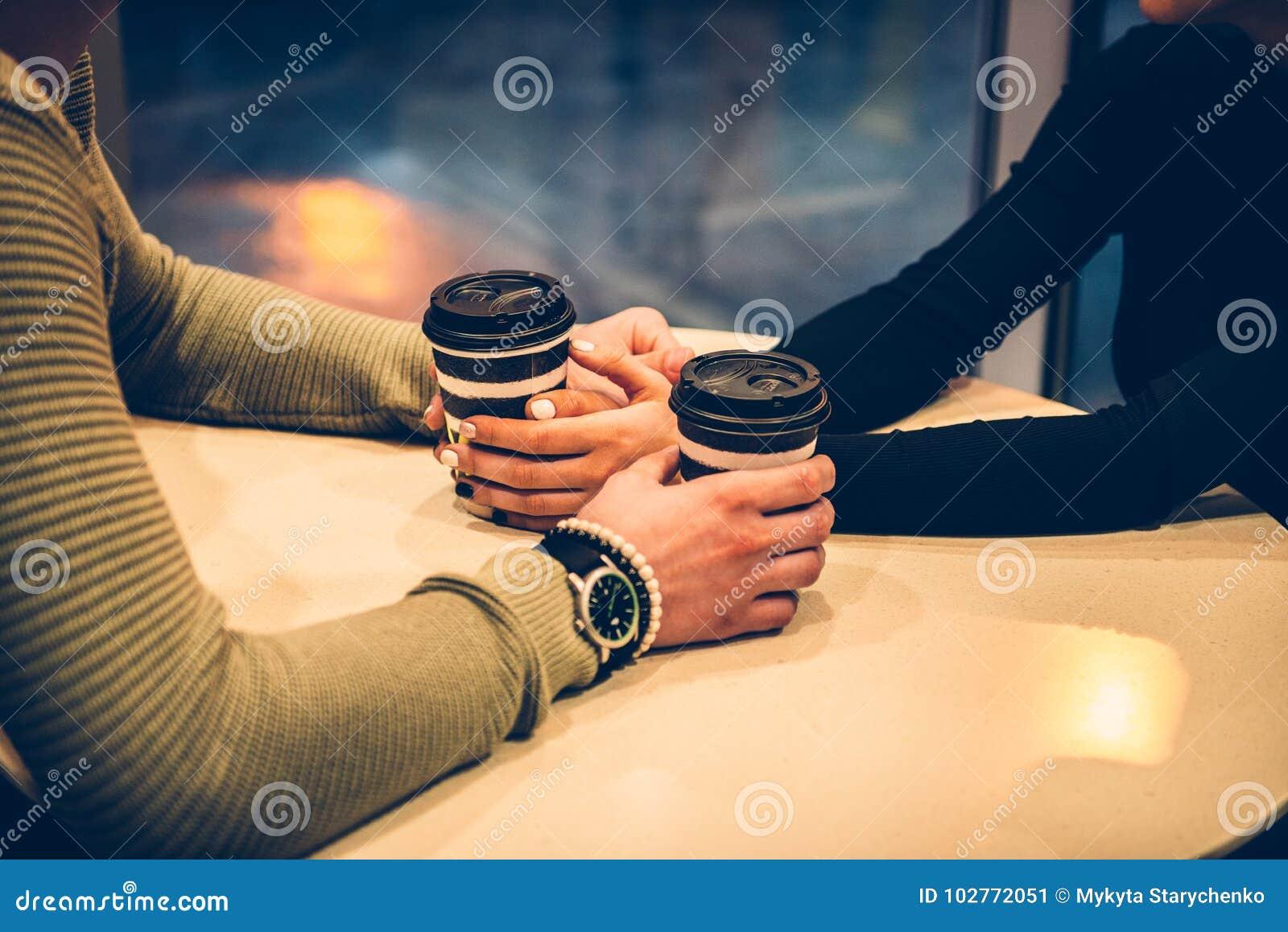 结合握手和喝在咖啡馆的咖啡