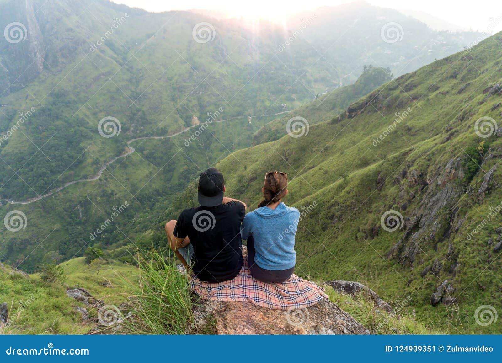 结合旅客男人和妇女坐峭壁,放松 山鸟瞰图