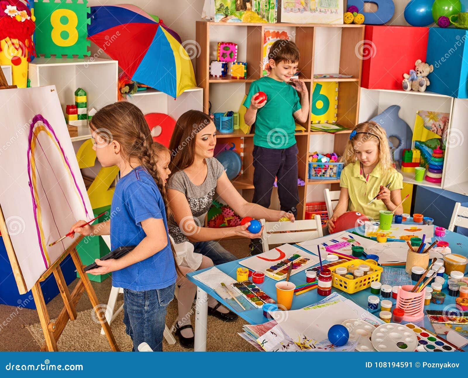 绘在画架的孩子手指 小组与老师的孩子
