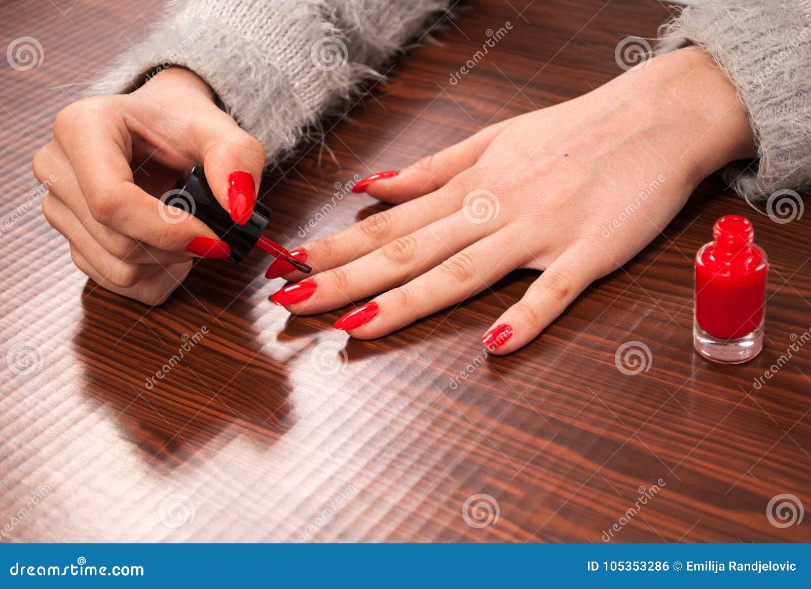绘她的在手指的妇女钉子在木书桌上的红颜色