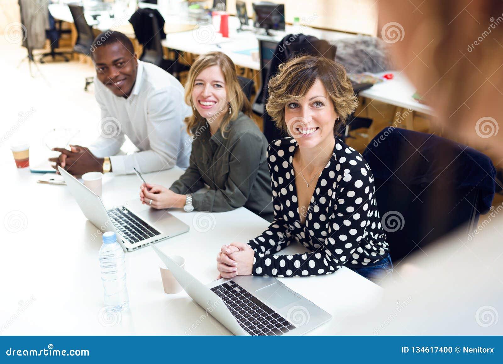 给予在会议的微笑的年轻买卖人注意关于coworking的地方