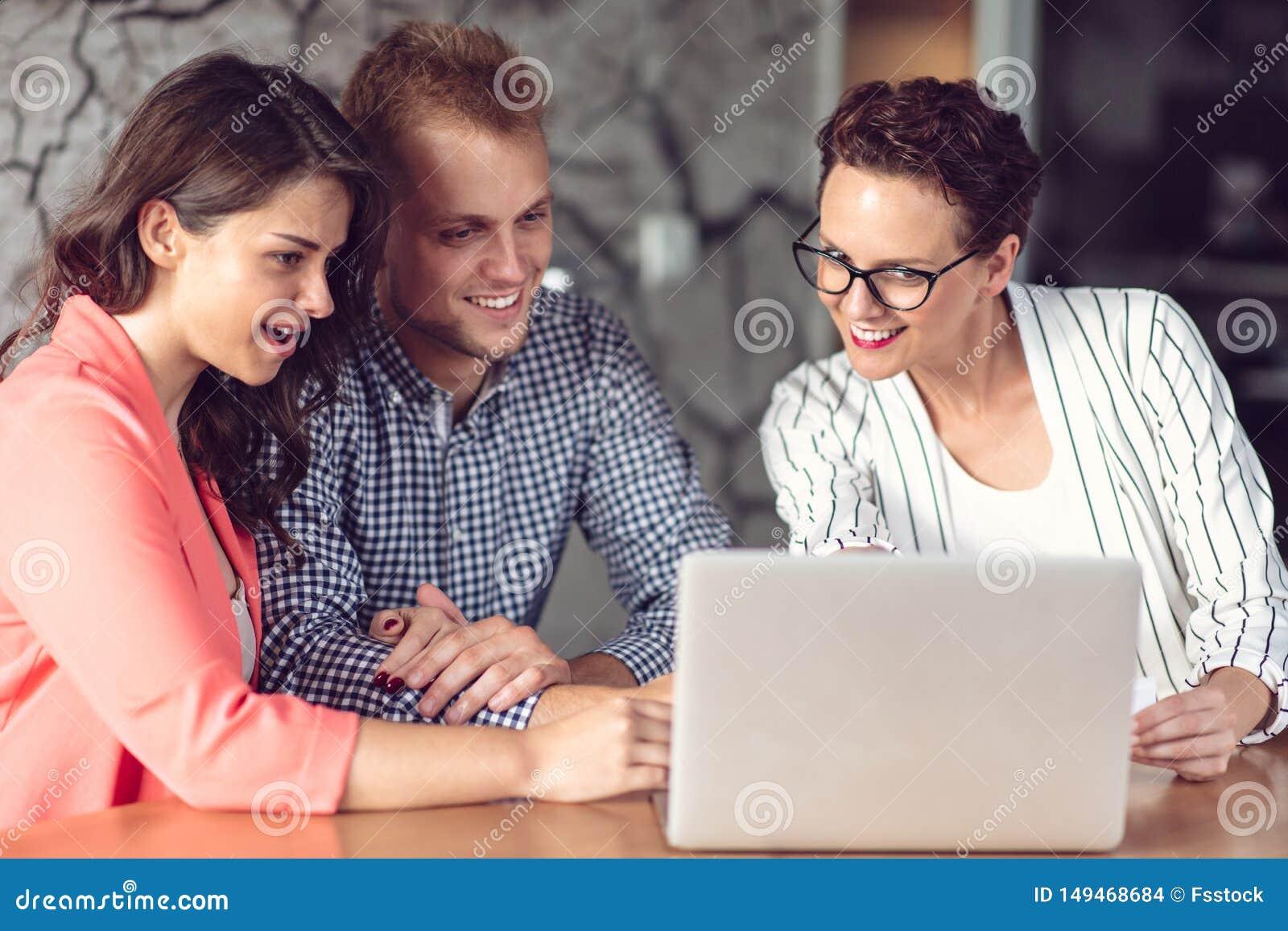 给介绍的投资顾问一对友好的微笑的年轻夫妇供以座位在她的书桌在办公室
