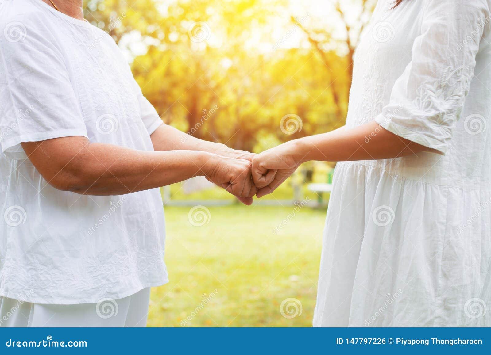 给拳头爆沸的亚裔妇女老人的手手年轻女人在室外在日落