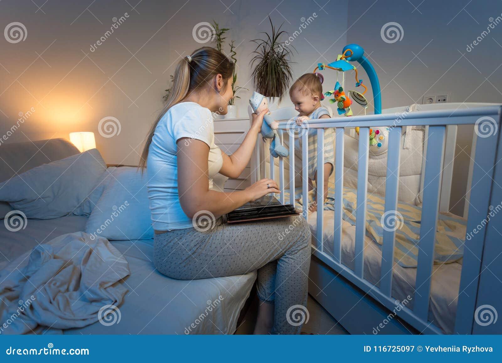 给玩具的美好的年轻母亲阅读书aand她的站立在轻便小床的小儿子在晚上