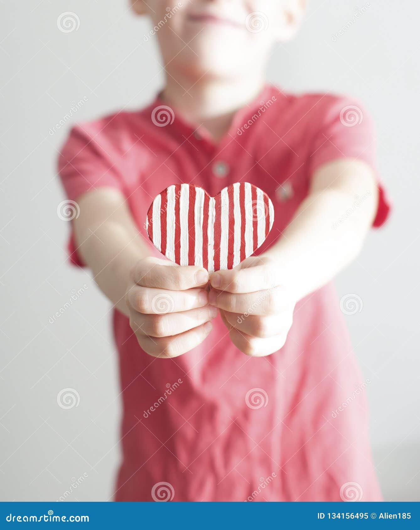 给红色被剥离的心形的愉快的男孩