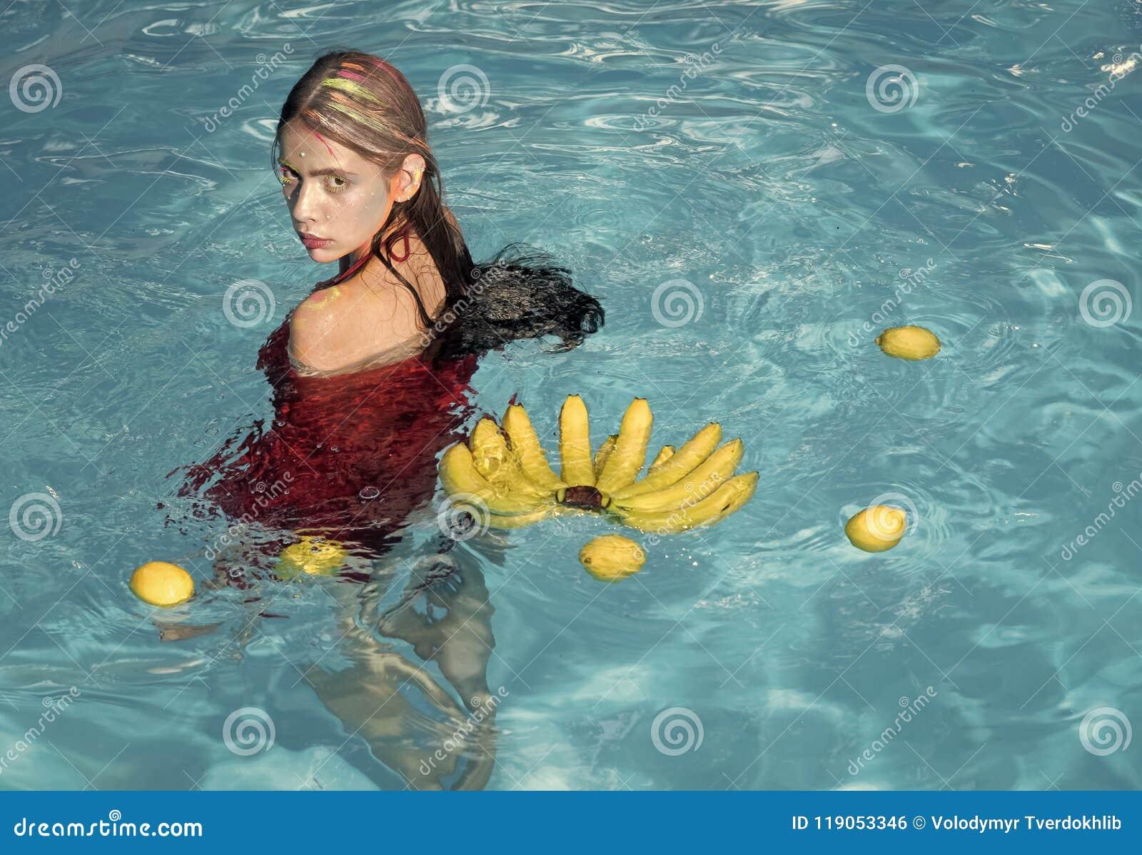 维生素和健康 暑假和旅行向海洋 在香蕉的维生素在坐在水附近的女孩 妇女放松