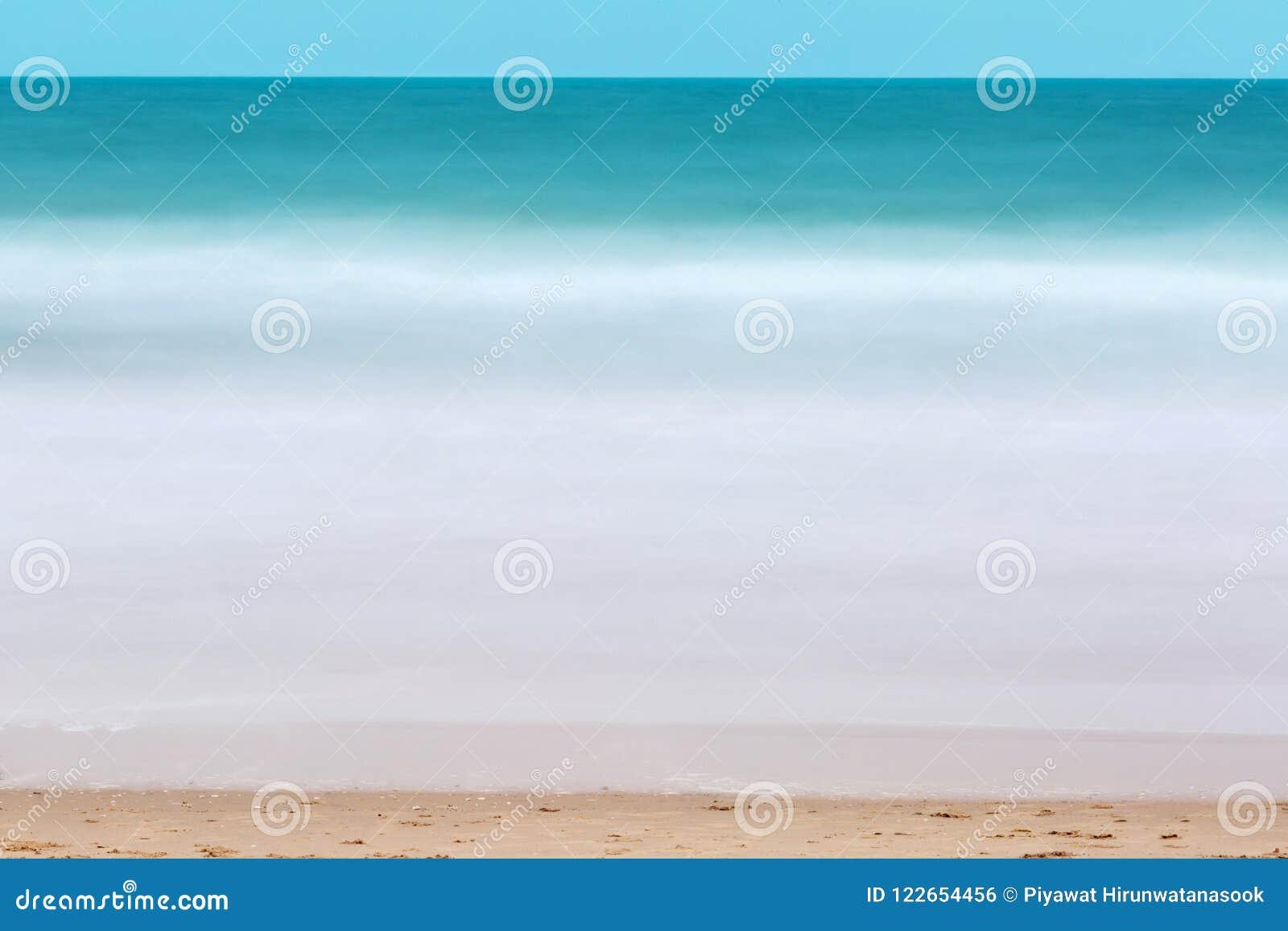 绿浪水流量表面和蓬松白色碎波采取与在海滩的长的曝光背景的