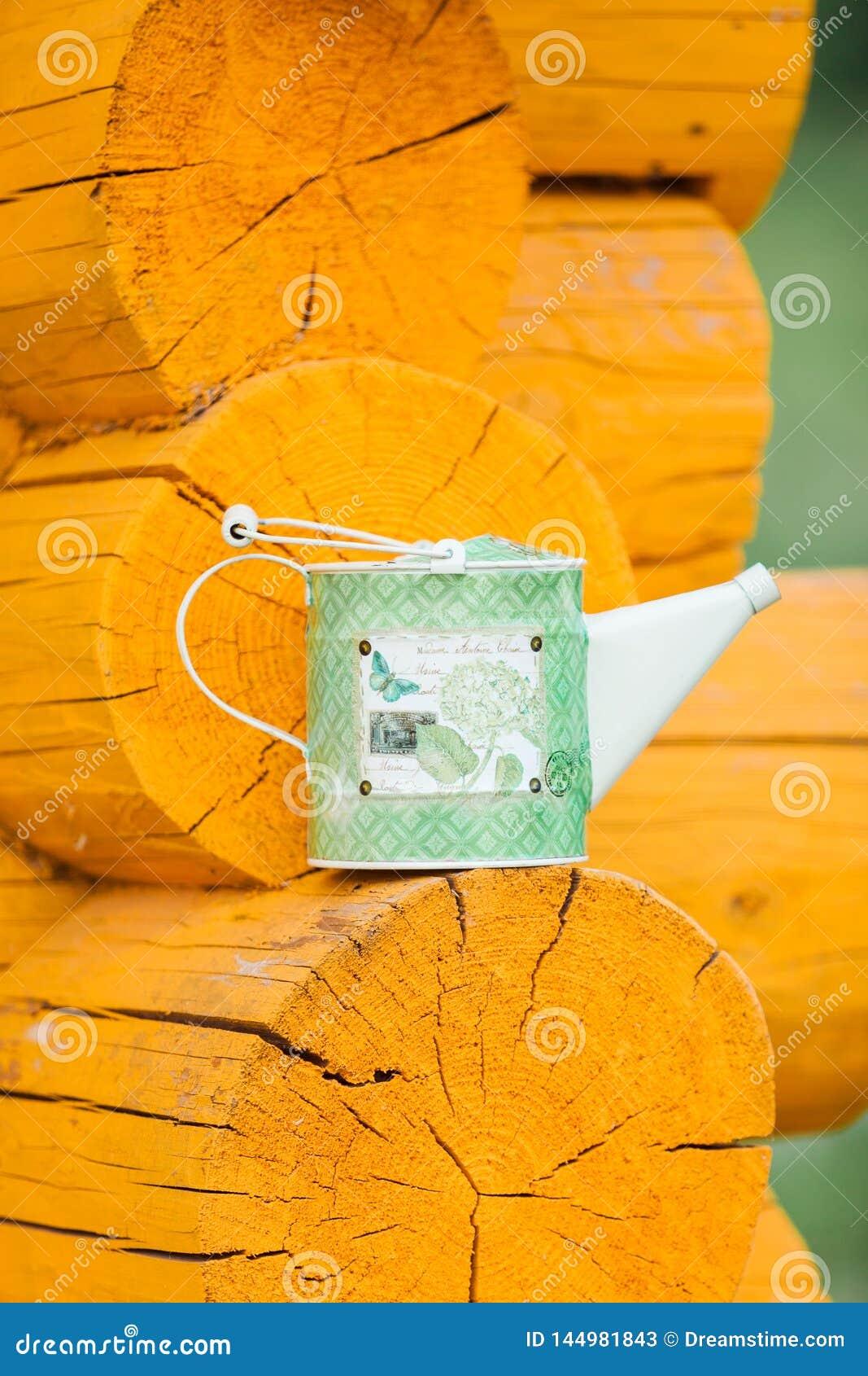 绿色喷壶在一个木壁架站立