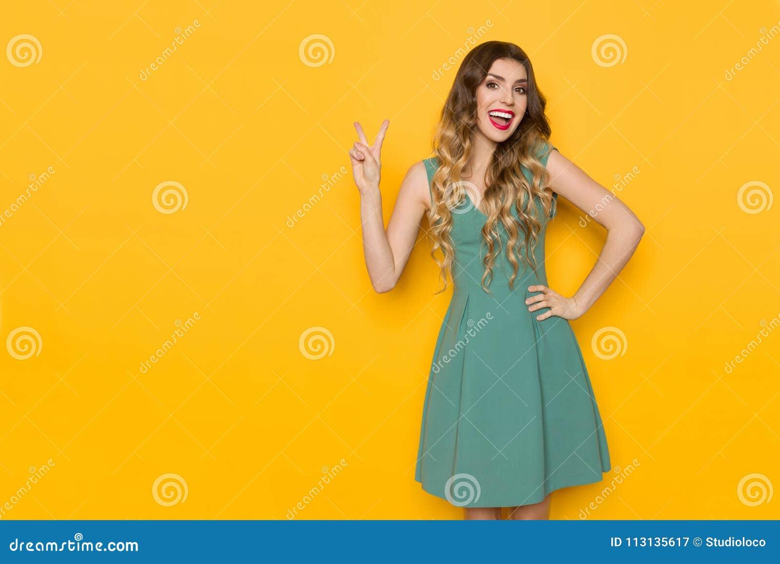绿色套衫连超短裙的笑的妇女显示和平手标志