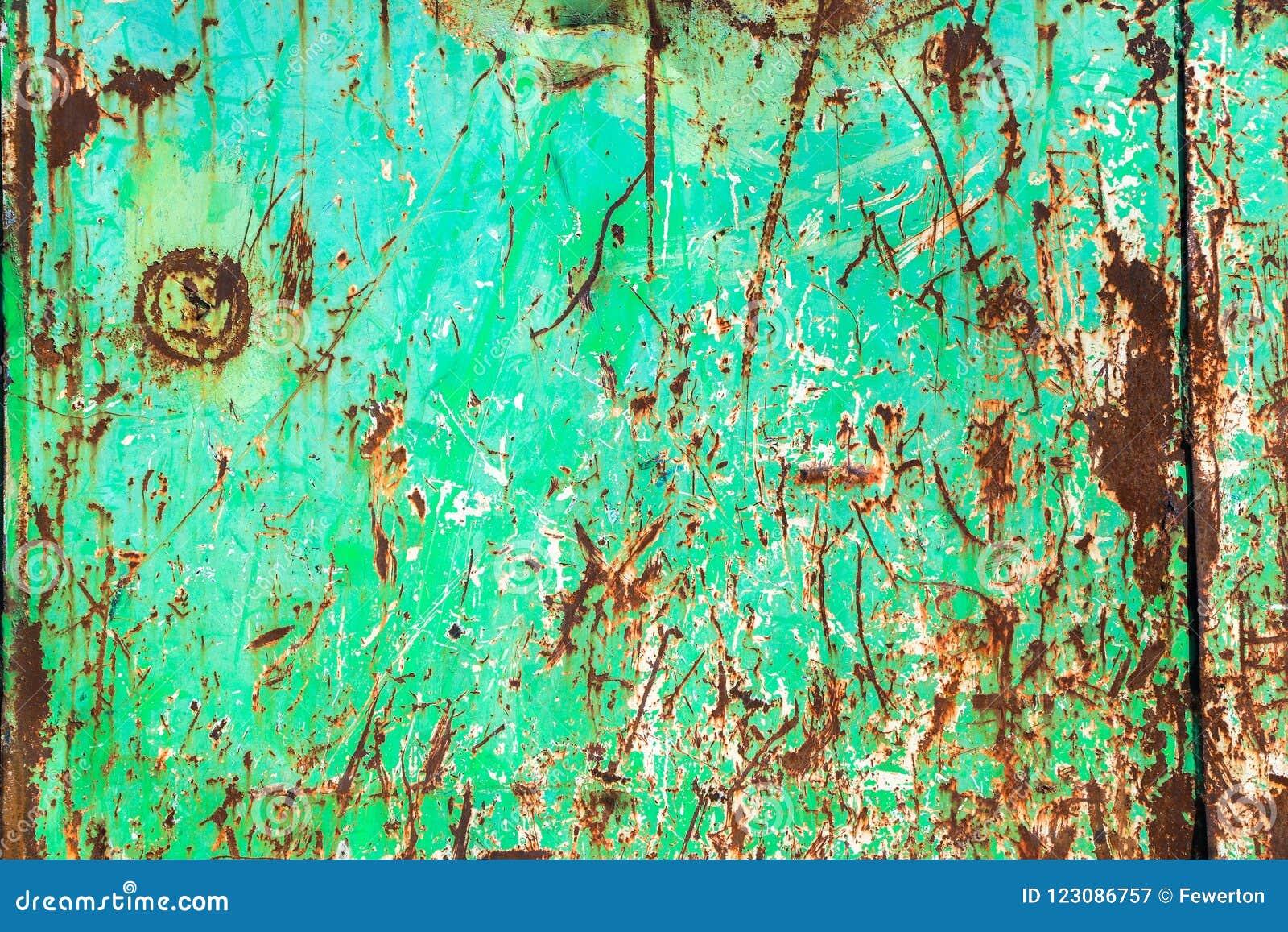 绿色生锈和脏的金属铁板材墙壁有典型的氧化铁红颜色的和有绿色削皮涂层油漆的