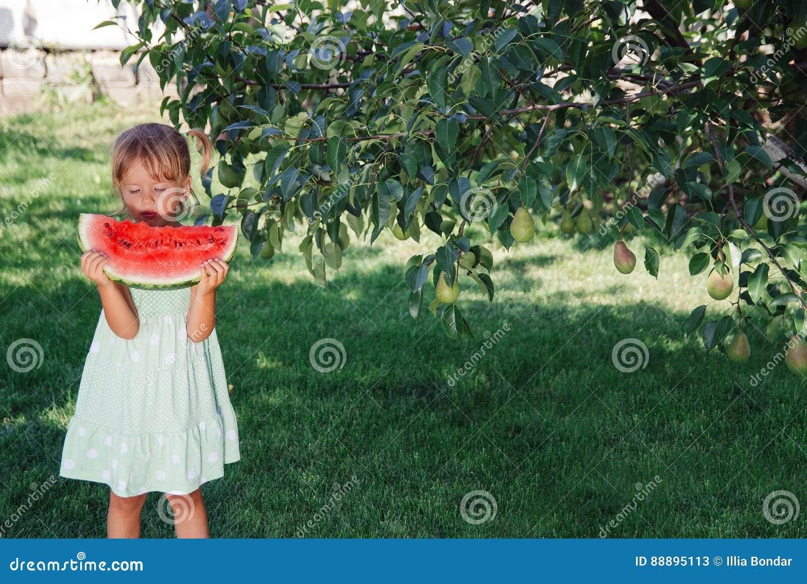 绿色礼服的小女孩,赤足站立在公园用大切片西瓜