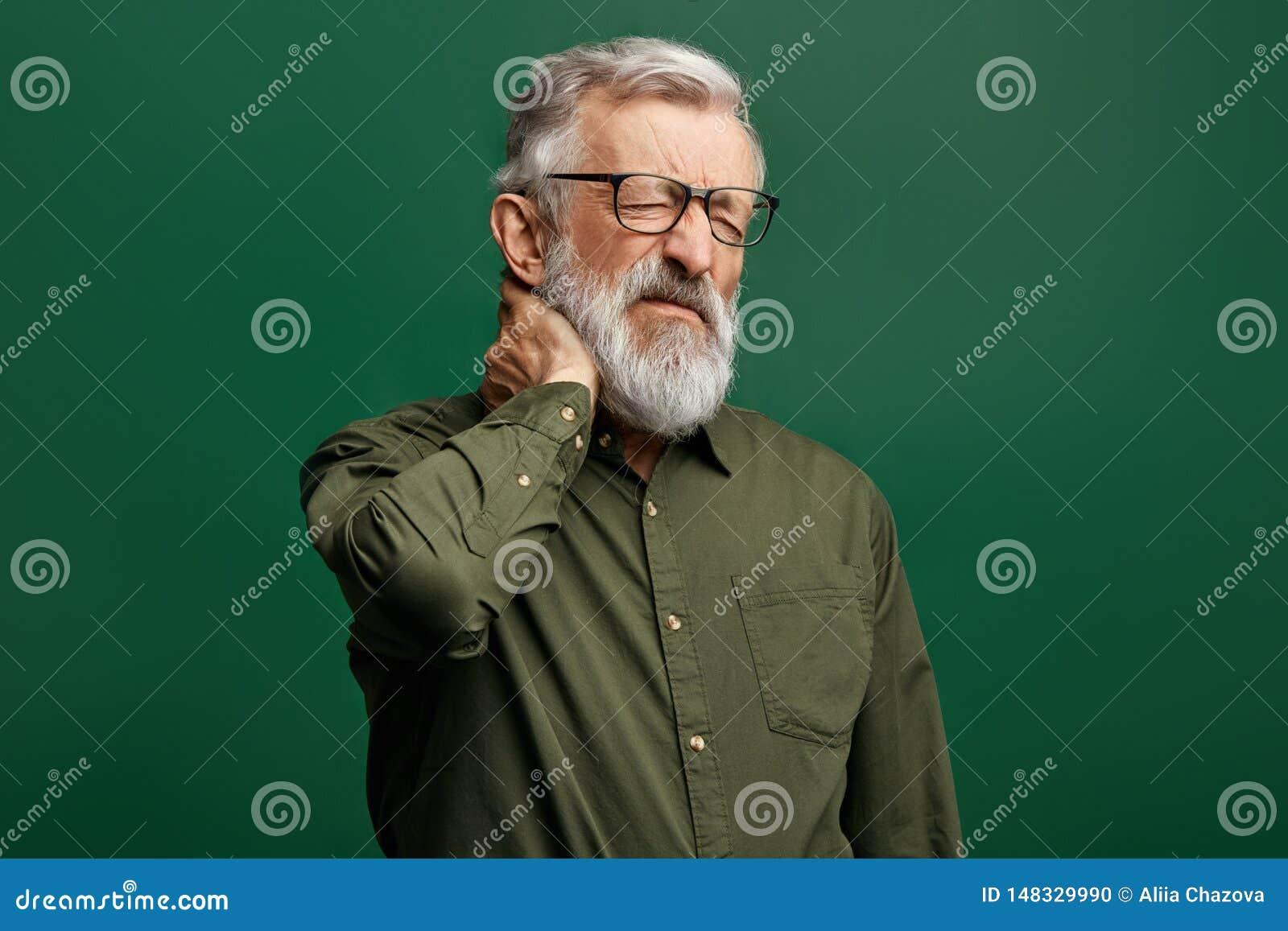 绿色衬衣的英俊的时髦的老人遭受脖子疼痛