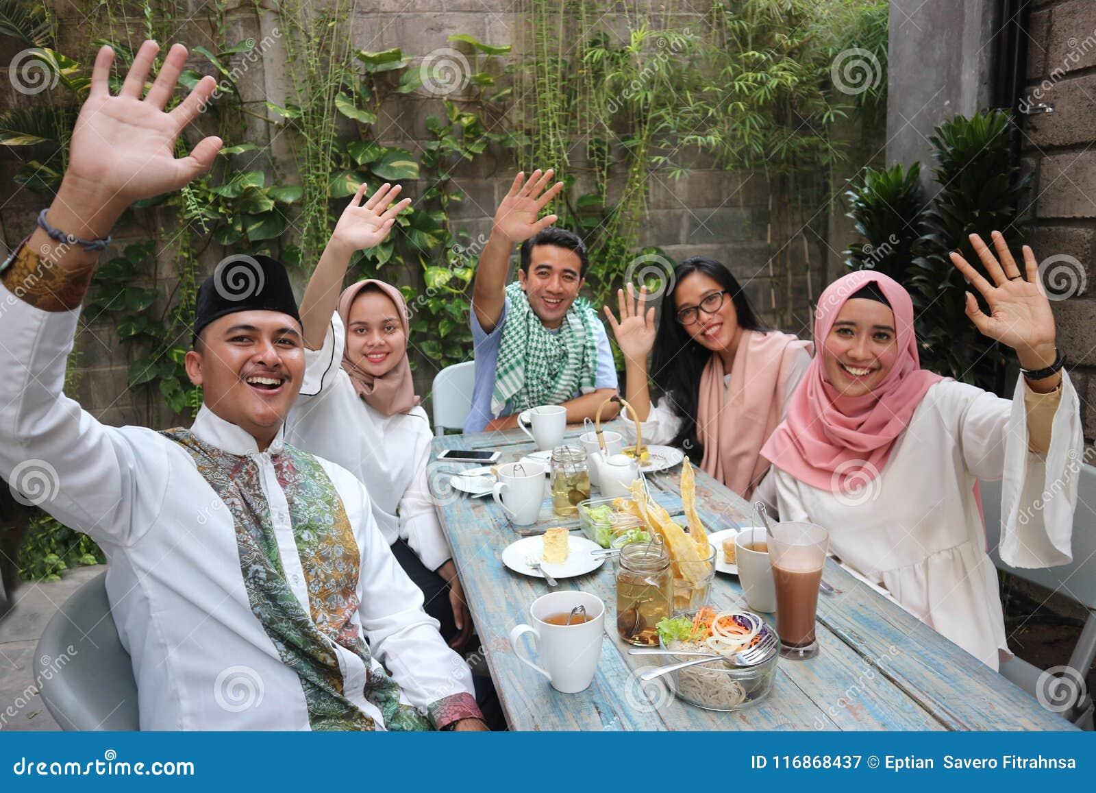 编组挥动在桌的愉快的年轻穆斯林用餐在赖买丹月c期间