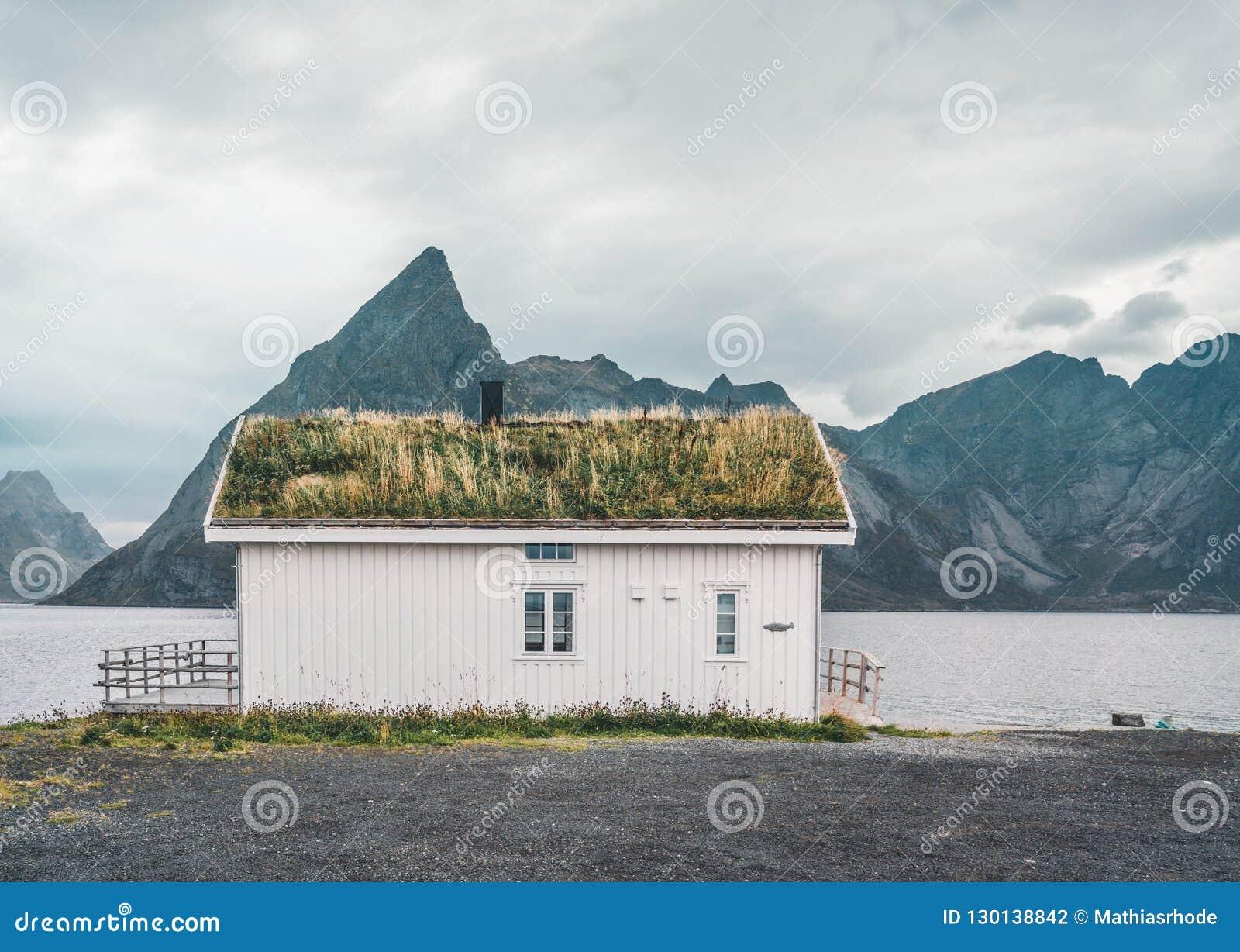 罗弗敦群岛海岛挪威- 2018年9月:有传统草屋顶和山的议院在多云的背景中