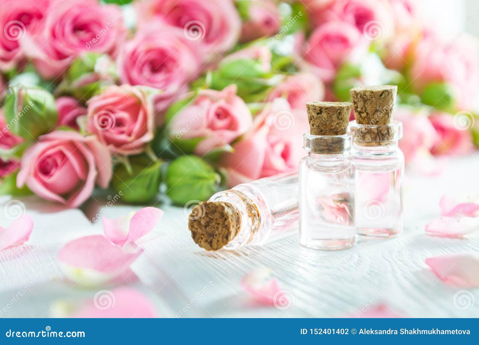 罗斯精油和玫瑰色花在白色木桌上