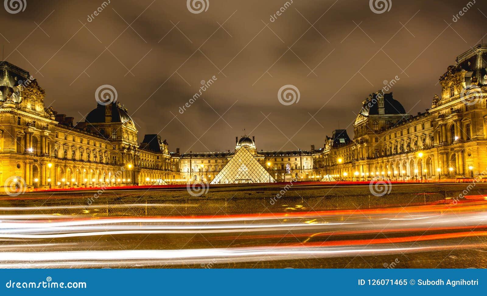 罗浮宫夜视图在巴黎,有汽车光的落后