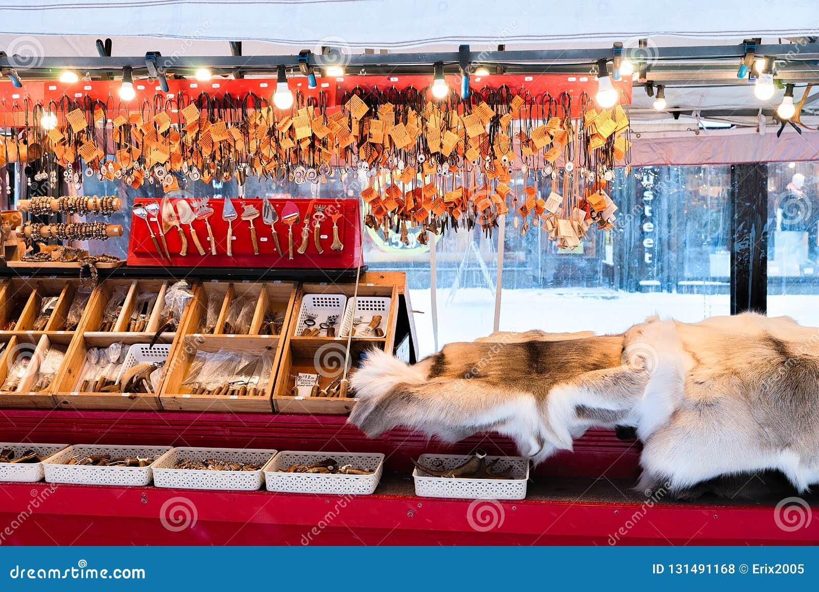 罗瓦涅米,芬兰- 2017年3月2日:冬天Saami纪念品例如驯鹿毛皮和垫铁在芬兰圣诞节市场,罗瓦涅米上,