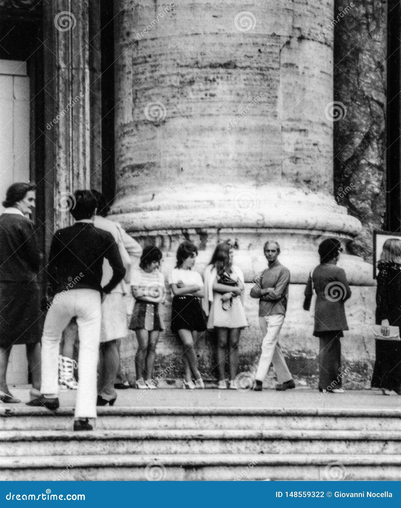 罗马,意大利,1970年-超短裙的三个女孩在人群休息在专栏的脚