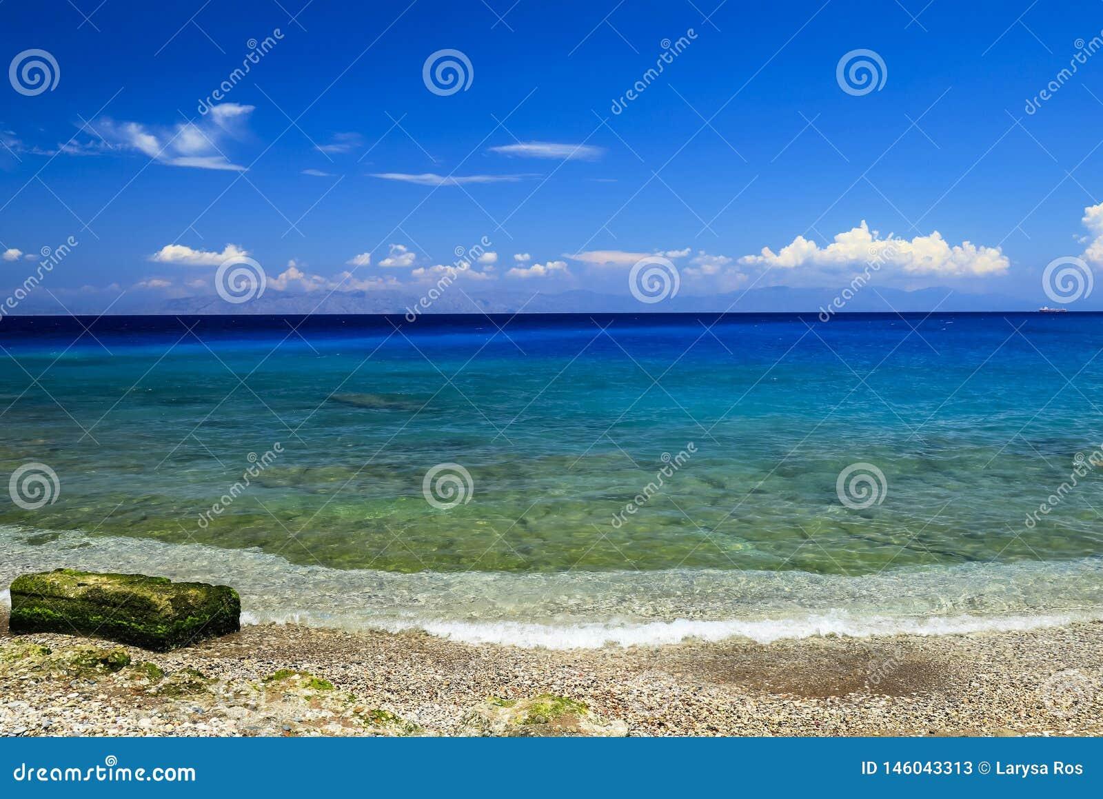 美丽如画的夏天海滩,在海浪线的岩石在罗得岛的,希腊,旅行,休闲,假期概念美丽的海 ?