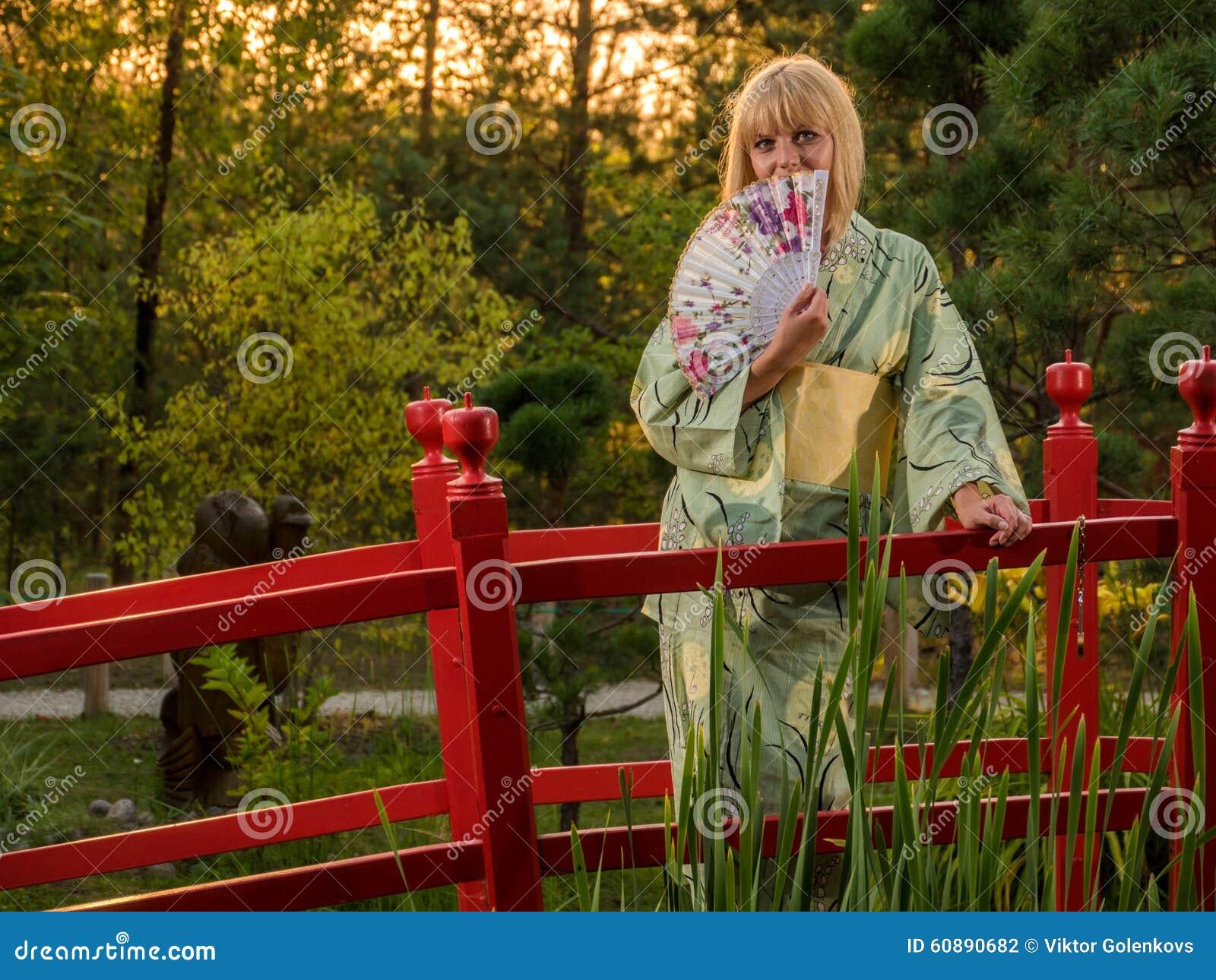 欧洲色情jjjcom_走在庭院和佩带的传统日本和服和黄色伞里的美丽的欧洲妇女.