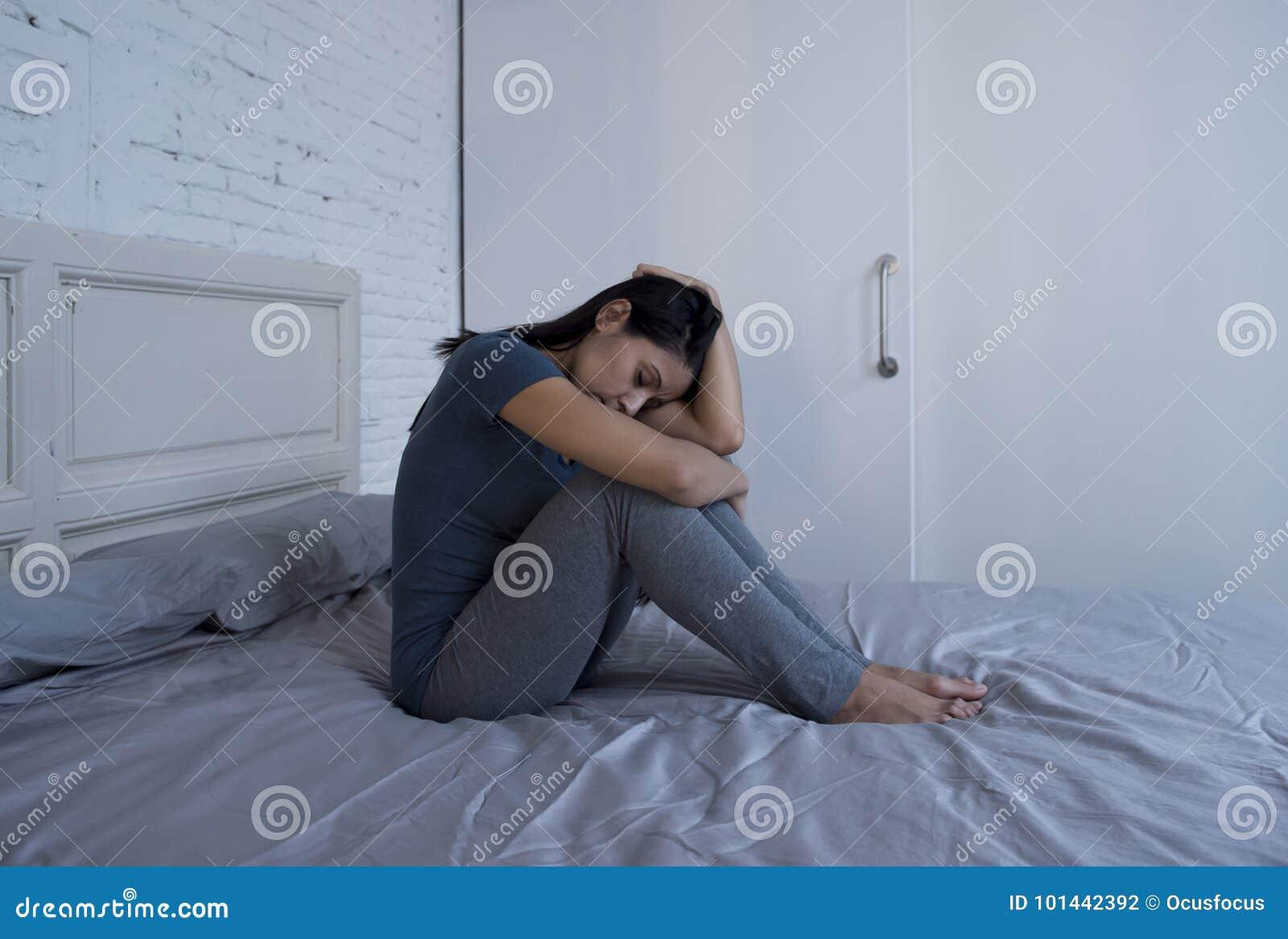 美丽的哀伤和沮丧的拉丁妇女在家坐床f