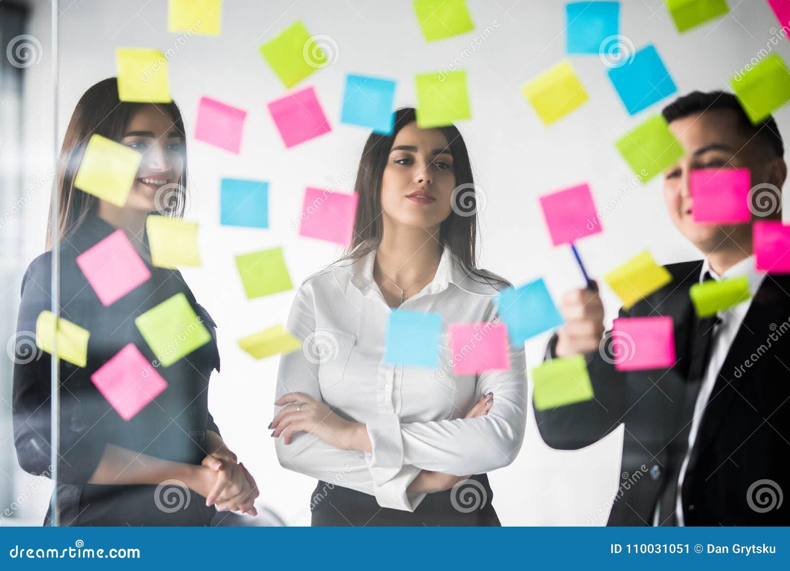 美丽的商人在办公室使用贴纸和标志,谈论想法并且微笑着在会议期间 小组工作