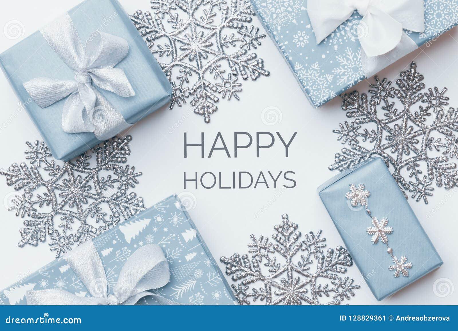 美丽的圣诞节在白色背景隔绝的礼物和银色雪花 淡色蓝色色的被包裹的xmas箱子